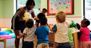 Teacher and children playing in the classroom using puppets