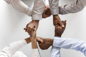 Several hands intertwined and holding to demonstrate reliability among customers and local movers that they hire.