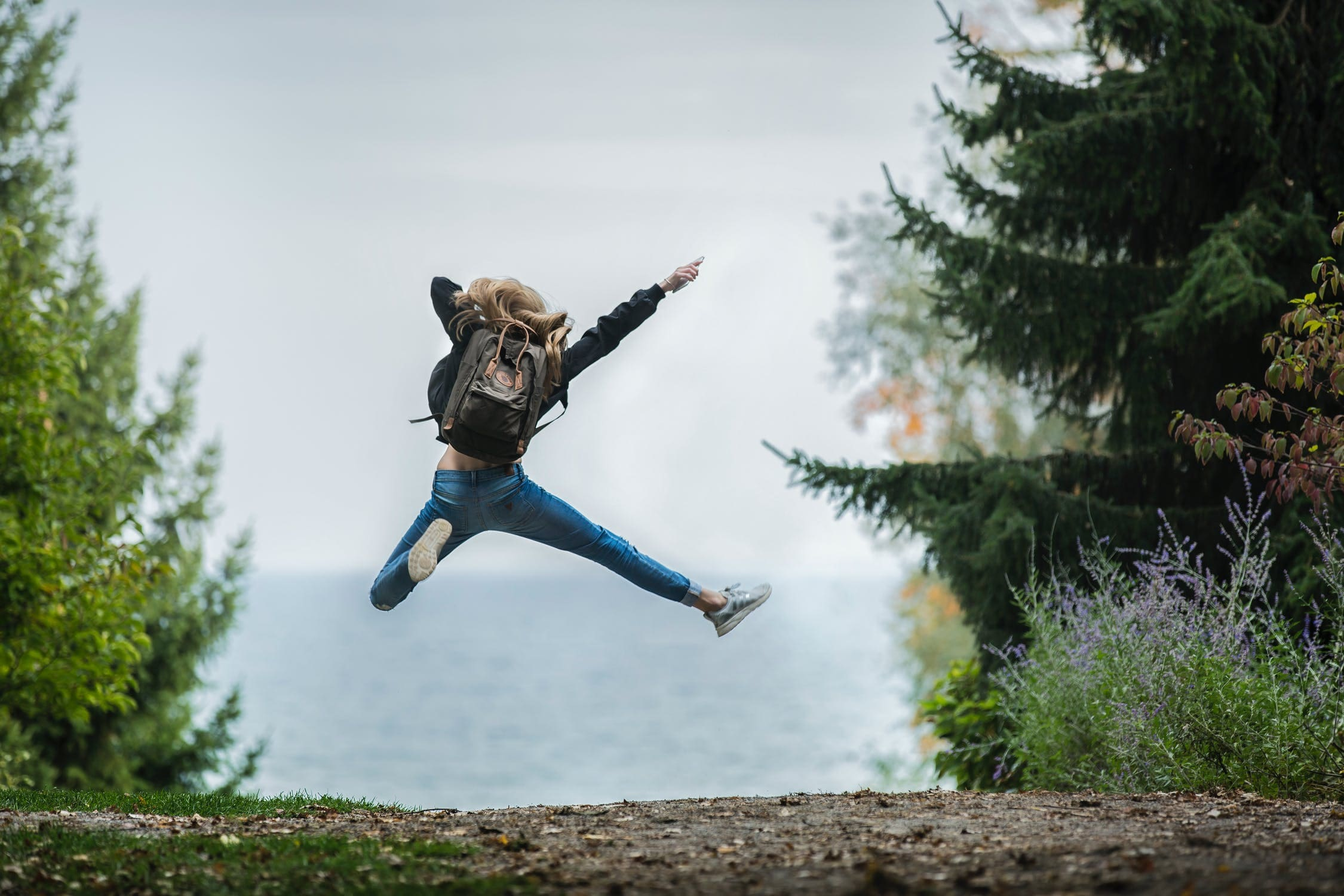 A woman jumping for joy from discovering one of the top cities for expats in New Jersey